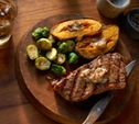 Image of Strip Steaks and Sweet Potatoes with Bourbon-Pecan Butter